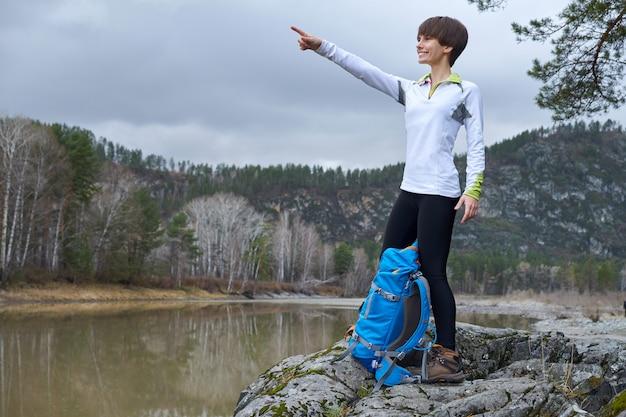 Mujer caminando con una mochila. apunte con su dedo a la distancia. retrato de deportes al aire libre