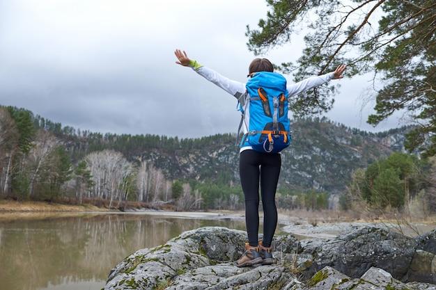 Mujer caminando con una mochila. manos a un lado. retrato de deportes al aire libre