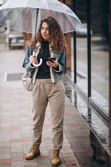 Mujer caminando bajo el paraguas en un clima lluvioso