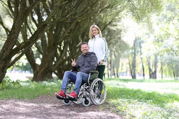 Mujer caminando en el parque con el hombre discapacitado en silla de ruedas creando una familia con personas con