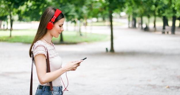 Mujer caminando en un parque mientras usa su teléfono inteligente para escuchar música