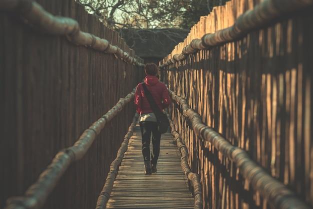 Mujer caminando en pasarela estrecha de madera