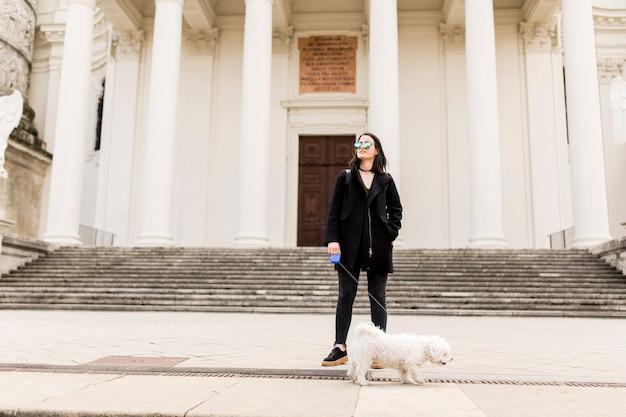 Mujer caminando con un perro en la calle