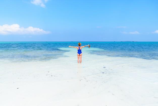 Mujer caminando en la playa tropical. vista trasera arena blanca