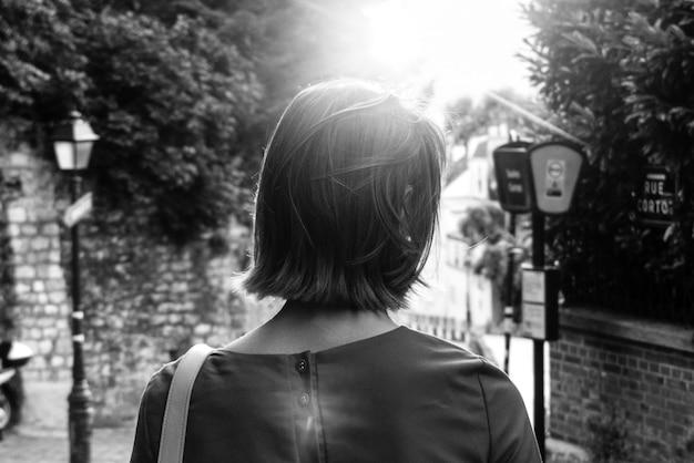 Mujer caminando hacia el poste de luz de la calle