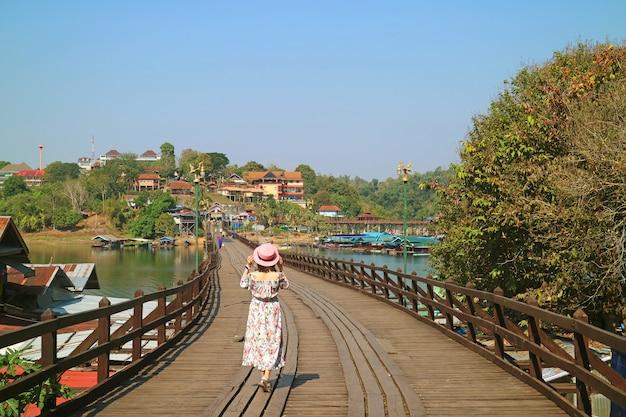 Mujer caminando por el puente de mon, el puente de madera más largo de tailandia en el distrito de sangkhlaburi