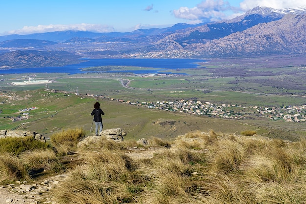 Mujer caminando por los senderos de la montaña hasta la cima, con hermosas vistas del paisaje. madrid.