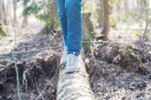 Mujer caminando sobre un tronco en el bosque y equilibrando: ejercicio físico, estilo de vida saludable y concepto de armonía