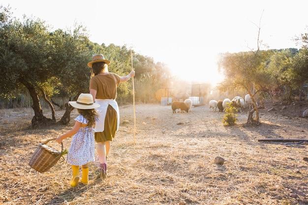 Mujer caminando con sus hijas arreando en el campo