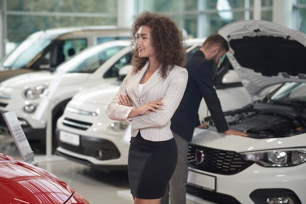 Mujer caminando en la tienda de automóviles, gerente de trabajo.