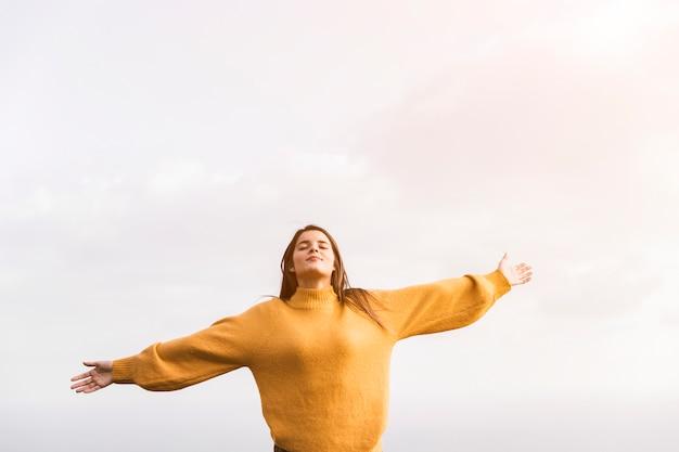 Una mujer caminante con los brazos extendidos disfrutando del aire fresco contra el cielo.