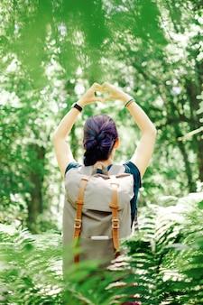 Mujer del caminante que hace forma del corazón con sus manos al aire libre.