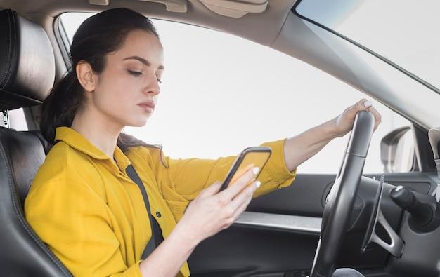 Mujer en camisa amarilla conduce y usa su teléfono