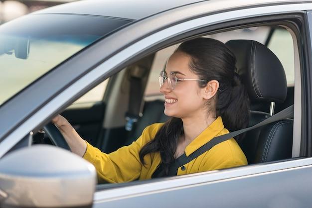 Mujer en camisa amarilla conduciendo