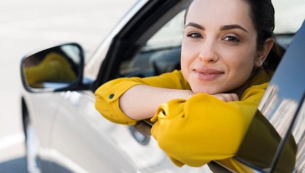 Mujer en camisa amarilla sentada en el auto