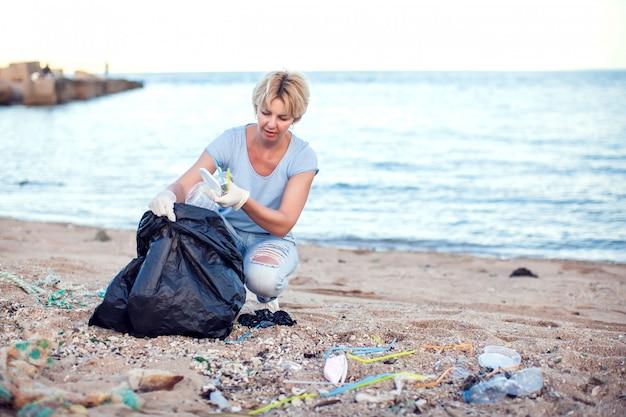 Mujer con camisa azul con guantes blancos y un gran paquete negro recogiendo basura en la playa. concepto de protección del medio ambiente y contaminación del planeta.