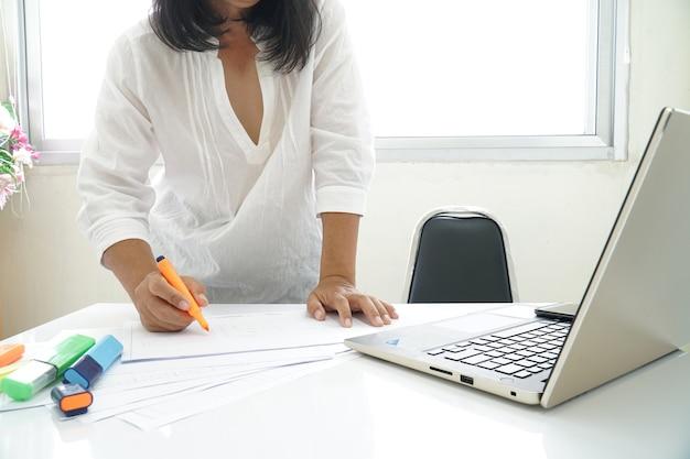 Una mujer con una camisa blanca comprobación de documentos