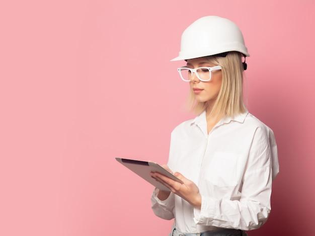 Mujer en camisa blanca, gafas y casco con tableta