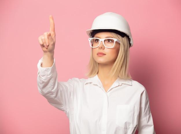Mujer de camisa blanca, gafas y casco