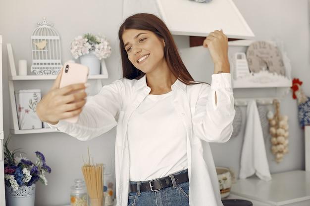 Mujer en una camisa blanca de pie en la cocina y haciendo una selfie