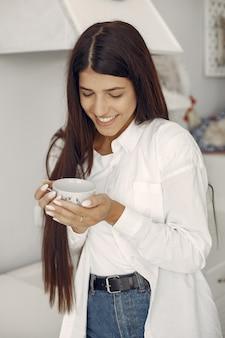 Mujer en una camisa blanca de pie en la cocina y tomando un café