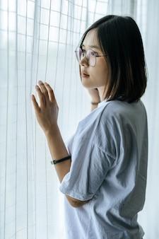 Mujer con una camisa blanca, de pie, coger una cortina cerca de la ventana.