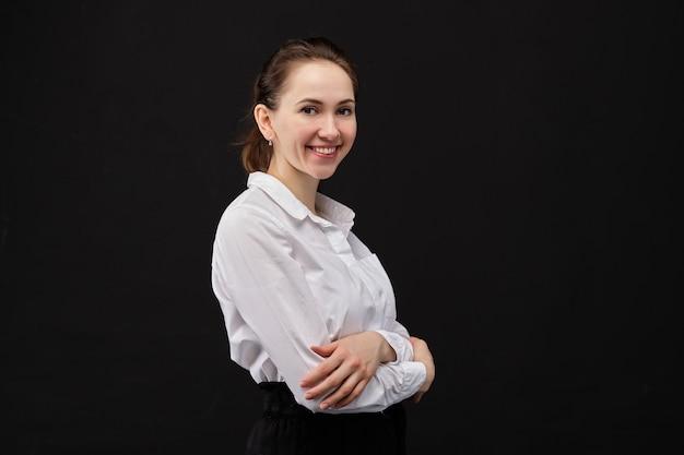 Una mujer con una camisa blanca sonríe