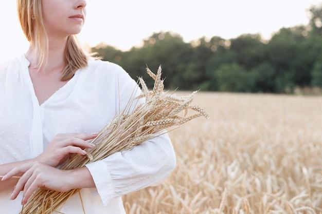 Una mujer con una camisa blanca sostiene trigo en un campo al atardecer. de cerca