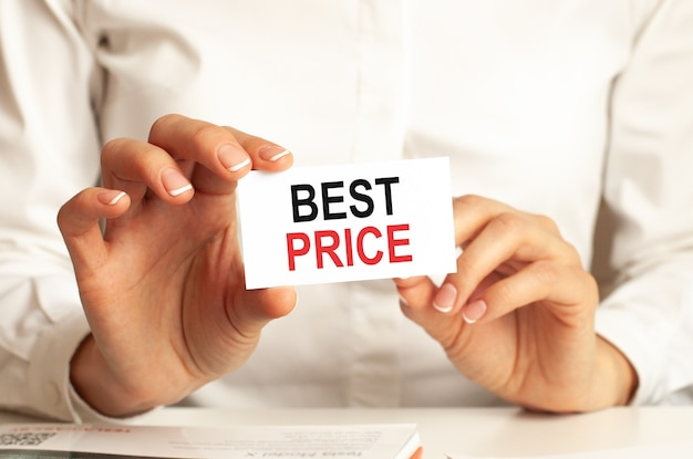 Una mujer con una camisa blanca sostiene un trozo de papel con el texto: mejor precio