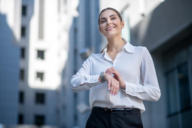 Mujer con camisa blanca tocando un reloj inteligente y mirando contento