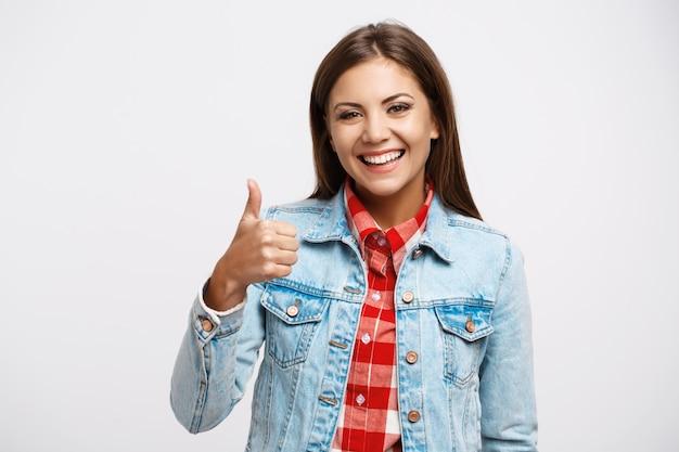 Mujer en camisa a cuadros y chaqueta vaquera muestra el pulgar hacia arriba