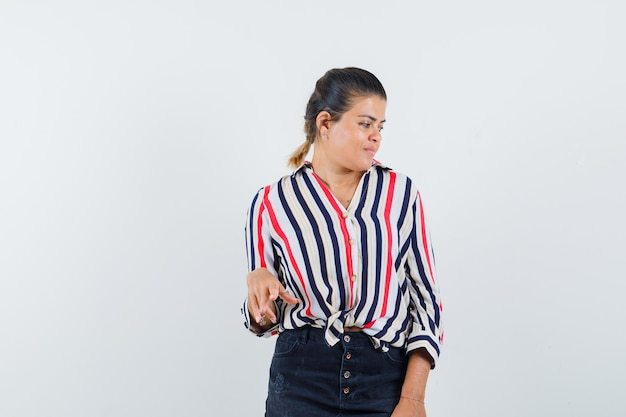Mujer en camisa, falda posando mientras mira a un lado y luciendo glamorosa