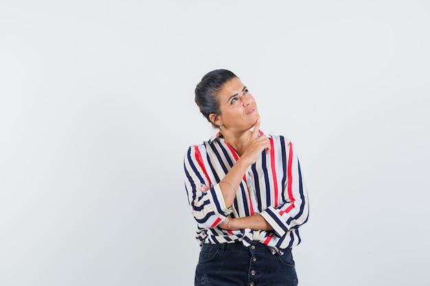 Mujer en camisa, falda sosteniendo el dedo en la barbilla y mirando soñadora