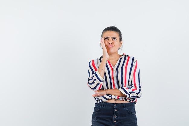 Mujer en camisa, falda sosteniendo la mano en la mejilla y mirando vacilante