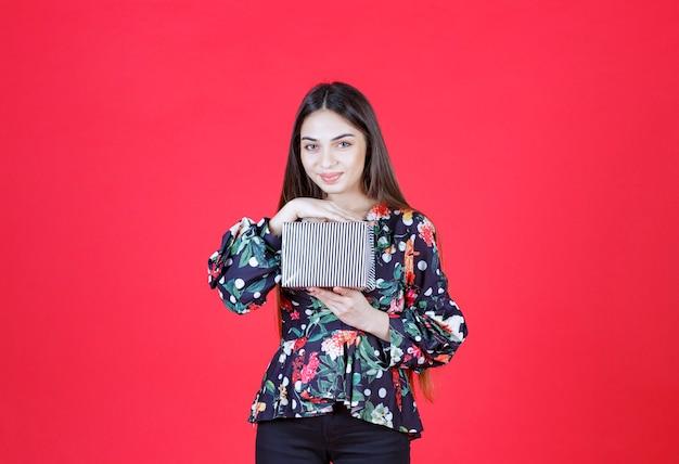 Mujer en camisa floral sosteniendo una caja de regalo plateada.