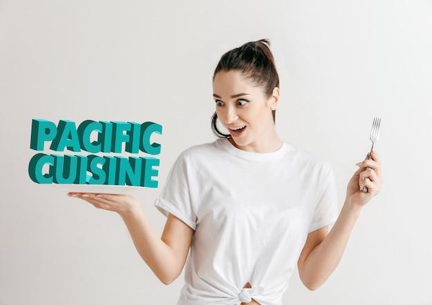 Mujer en camisa con la gente aislada en blanco. modelo femenino sosteniendo un plato con letras de la palabra cocina del pacífico. elegir una alimentación saludable, una dieta, una nutrición orgánica y un estilo de vida amigable con la naturaleza.