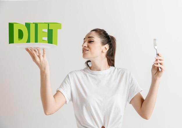 Mujer en camisa con la gente aislada en blanco. modelo femenino sosteniendo un plato con letras de la palabra dieta. elegir una alimentación saludable, una dieta, una nutrición orgánica y un estilo de vida amigable con la naturaleza.