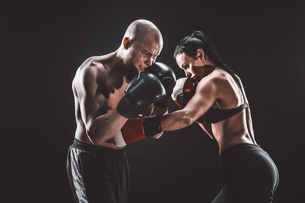 Mujer sin camisa haciendo ejercicio con el entrenador en la lección de boxeo y defensa personal, estudio, espacio oscuro