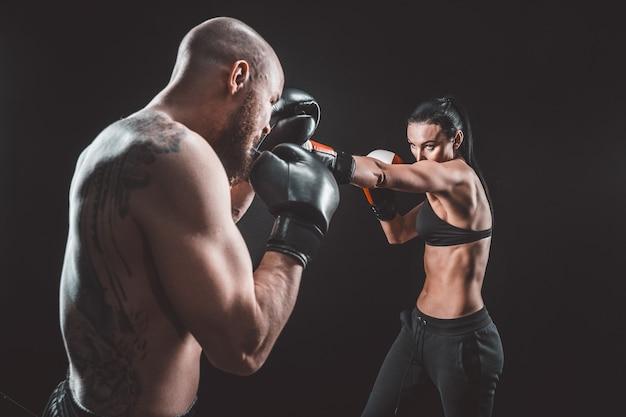 Mujer sin camisa haciendo ejercicio con el entrenador en la lección de boxeo y defensa personal, estudio, humo en el espacio