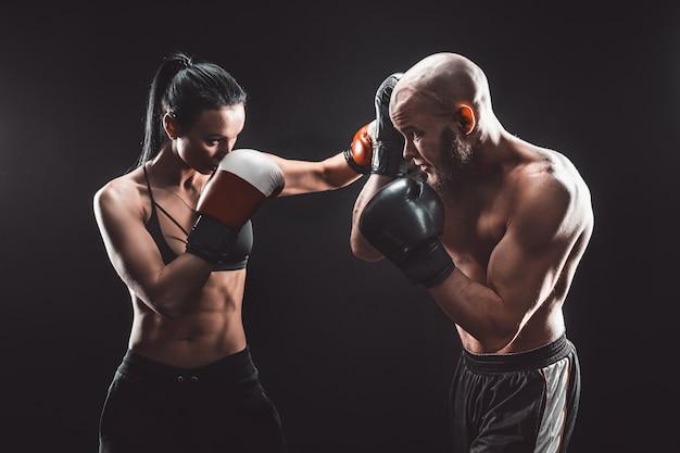 Mujer sin camisa haciendo ejercicio con un entrenador en la lección de boxeo y defensa personal lucha femenina y masculina