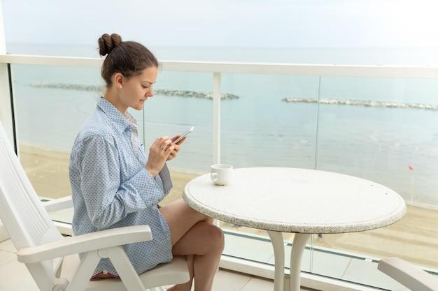 Mujer en camisa de hombre con teléfono inteligente en la terraza de su casa