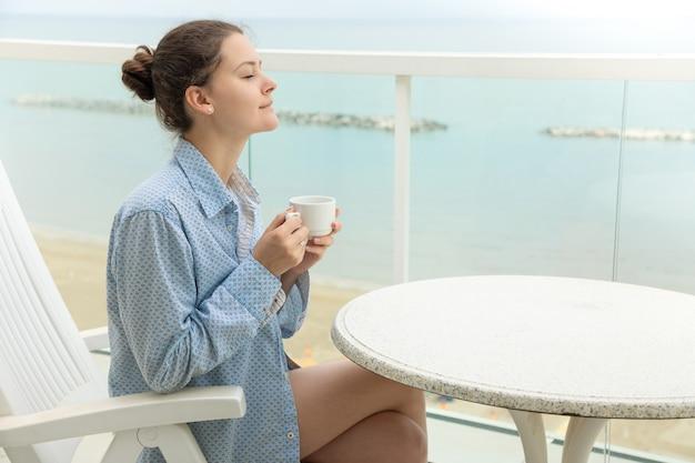 Mujer en camisa de hombre tomando café en la terraza de su casa