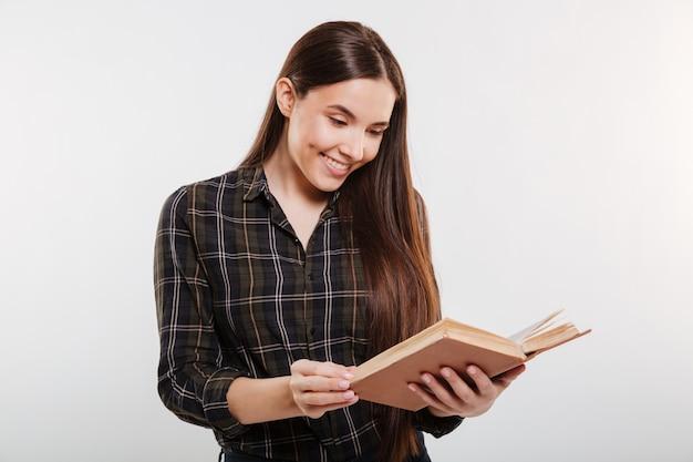 Mujer en camisa leyendo libro