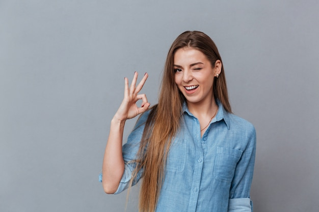 Mujer en camisa mostrando signo ok