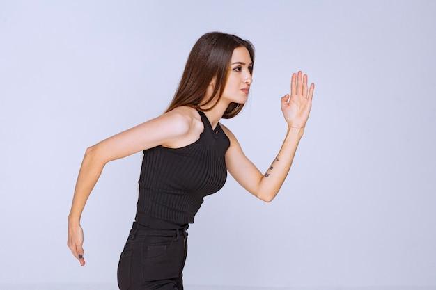 Mujer con camisa negra corriendo o escapando.