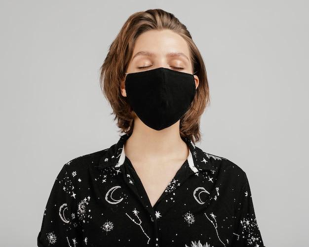 Mujer con camisa negra y máscara