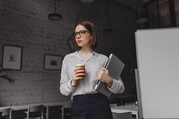 Mujer en camisa y pantalones de oficina posa con una taza de café y tiene un portátil. foto de niña de pelo corto con gafas en oficina brillante.