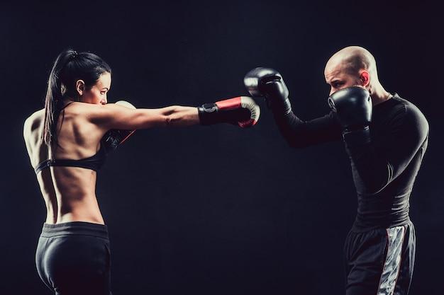 Mujer sin camisa que ejercita con el entrenador en la lección de boxeo y defensa personal, estudio, fondo oscuro. lucha femenina y masculina.