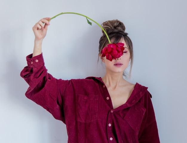 Mujer en camisa roja que agujerea la peonía roja