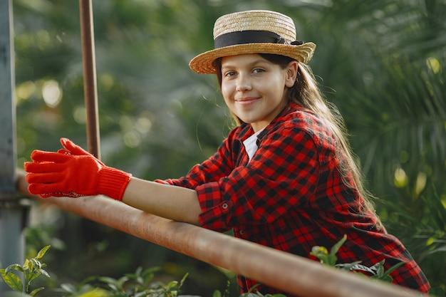 Mujer con camisa roja. trabajador con macetas. hija con plantas